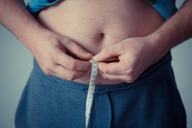 a person measuring their belly