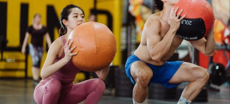 A man and a woman doing the wall ball exercise as one of the top CrossFit workouts to improve your endurance.