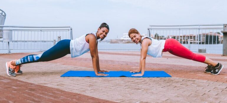 Two women doing the plank sidewalk.
