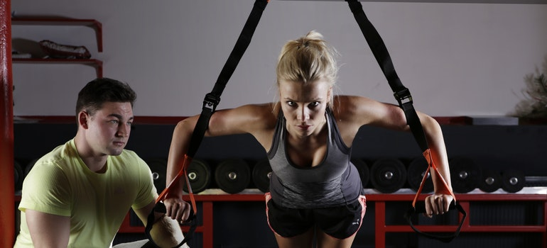 A woman working out with her personal trainer feeling motivated because she chose a trainer that posesses all essential qualities to look for in a good personal trainer.