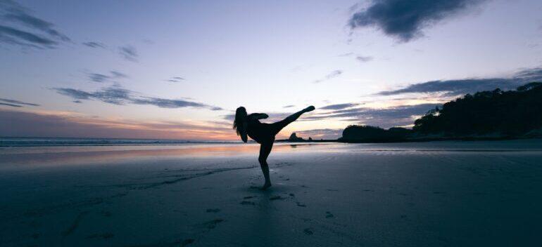 a girl doing Karate on the beach