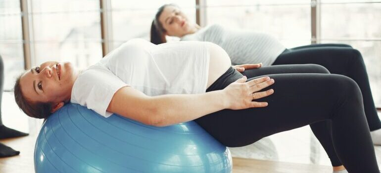 Two women doing pregnancy lower back pain relief exercises.