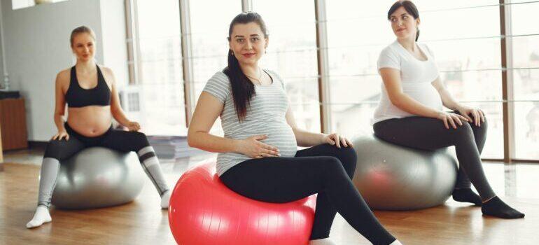 3 pregnant ladies preparing for yoga class