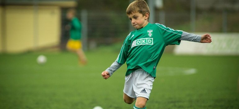 A child chasing a ball while playing football.