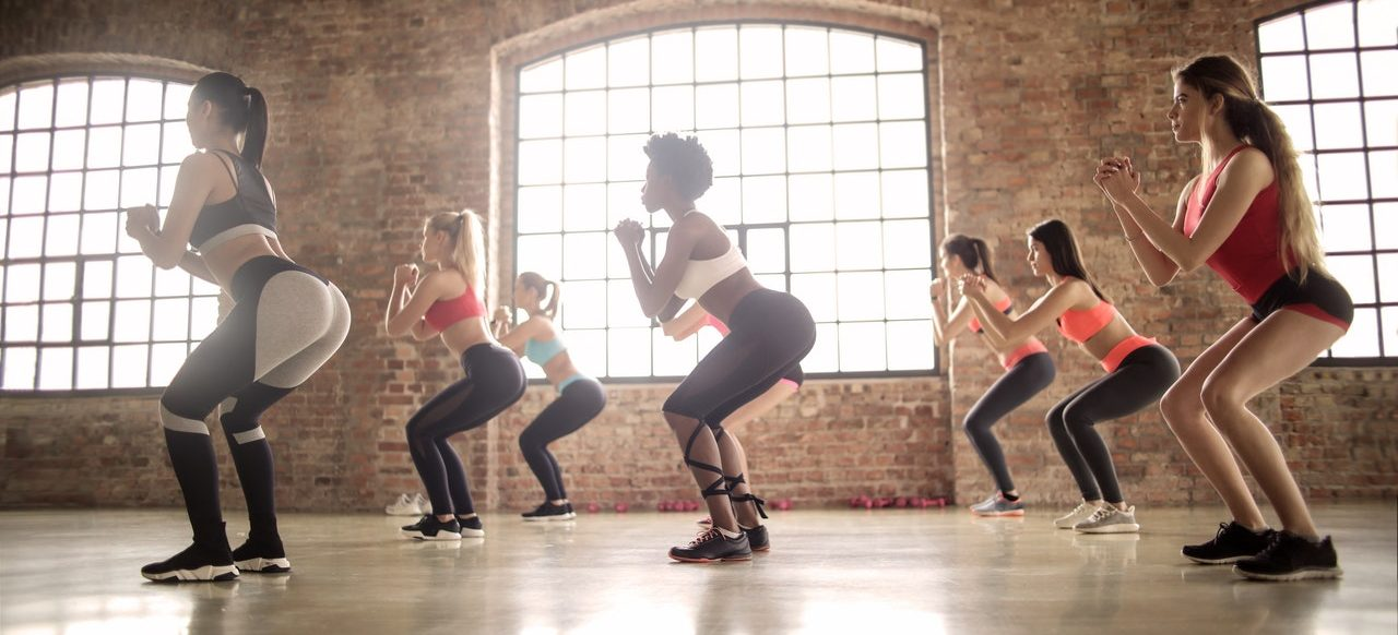 A group of women doing squats.