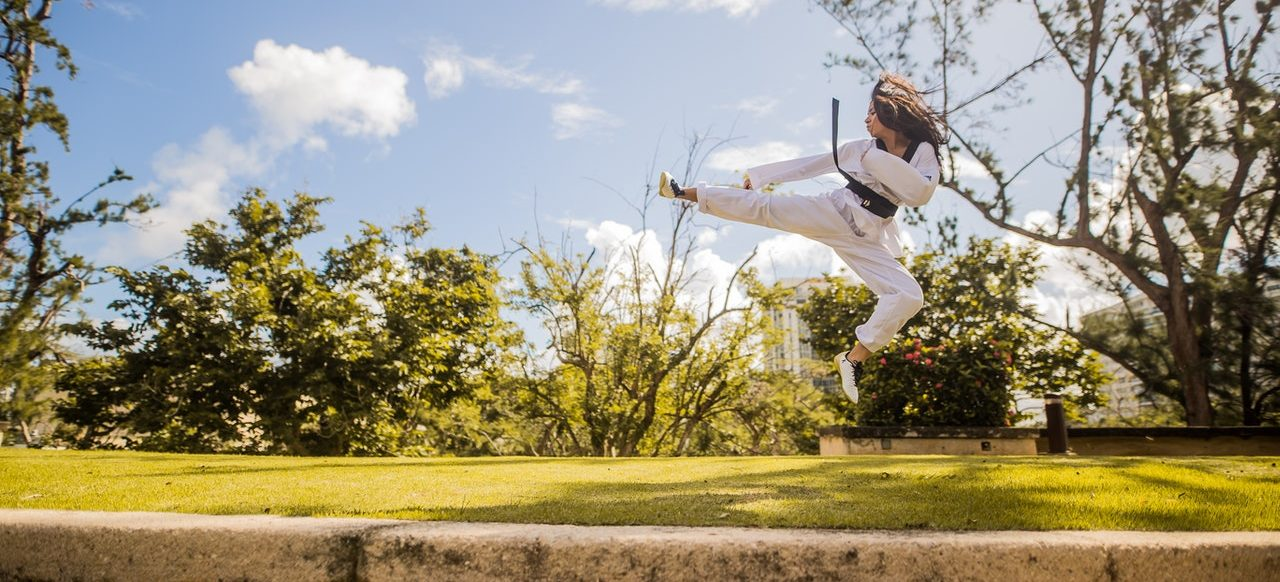 A woman doing an impressive karate move in nature demonstrating the effect of karate training on flexibility and muscle strength.
