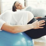 two pregnant women doing yoga