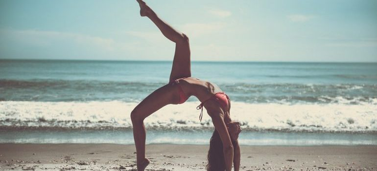 A girl on the beach doing power yoga for weight loss.