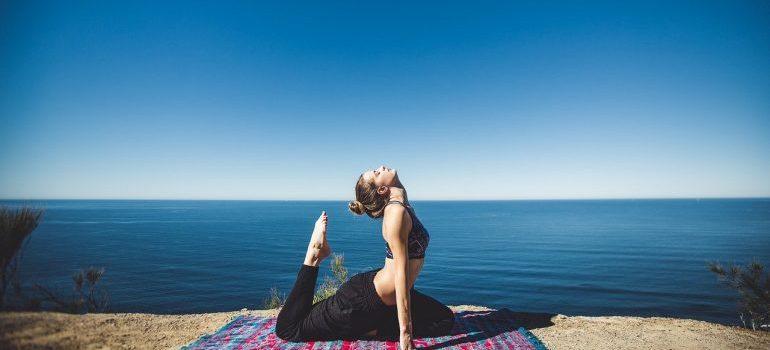 A woman doing yoga near the ocean.