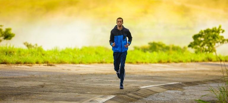 A man jogging keeping good heart rate, one of the health benefits of football for men.