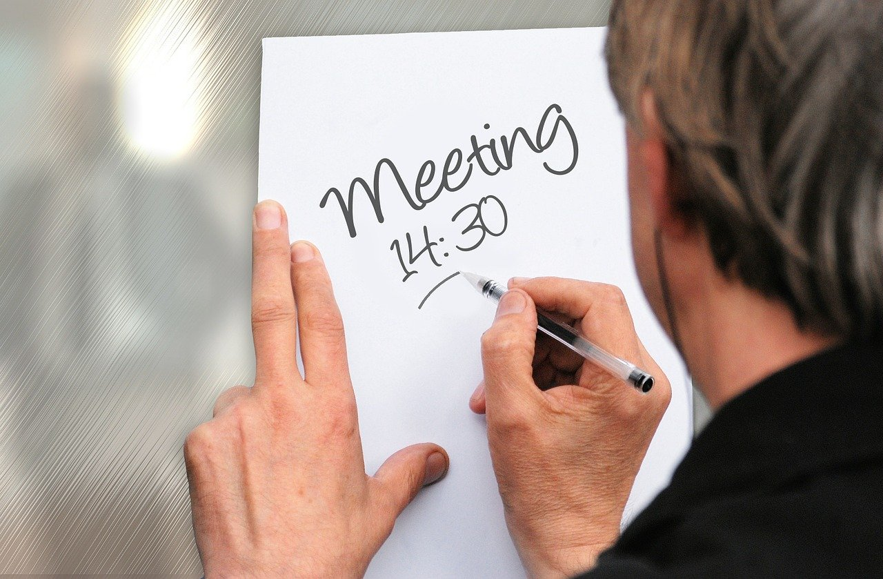 A person writing down a meeting