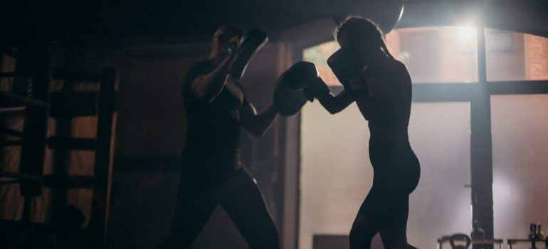 Young woman and her trainer sparring.