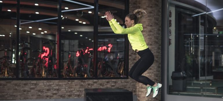 a woman jumping on a mattress as one of many crossfit workouts you can do at home