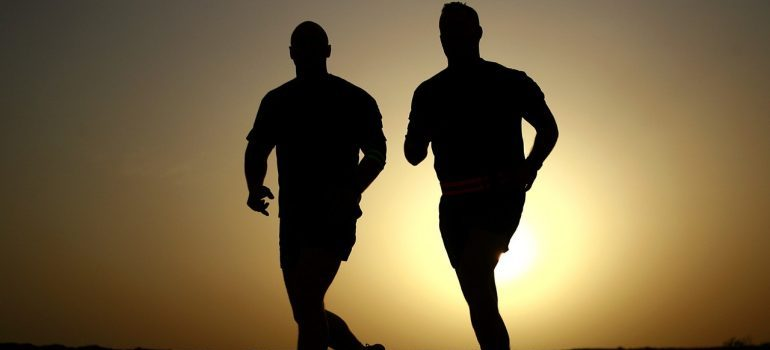 Two men jogging at sunrise