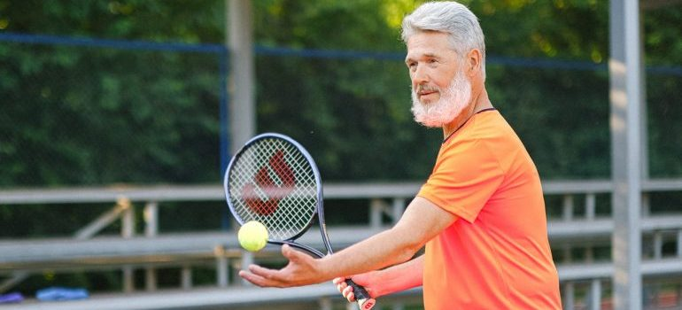 An elderly man playing tennis.