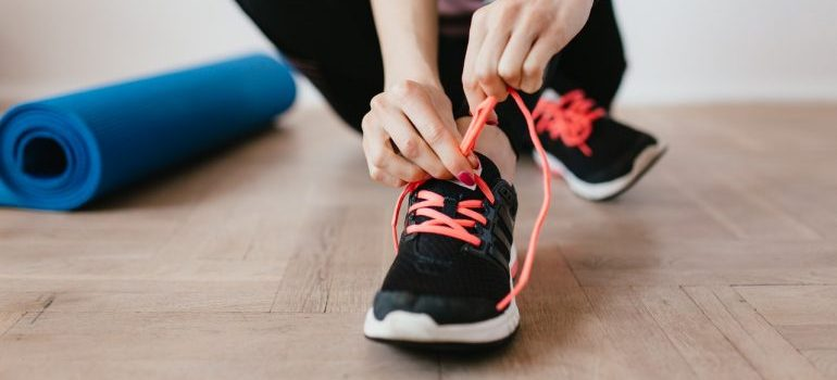 woman holding shoelace on her shoes