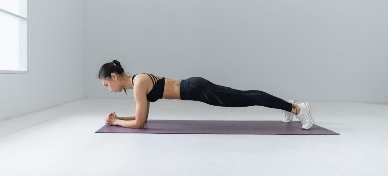 a woman doing a plank on a yoga mat