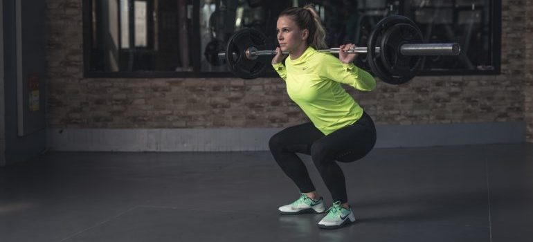 woman doing squats with weight