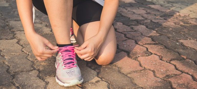 woman tieing shoelaces on her running shoes
