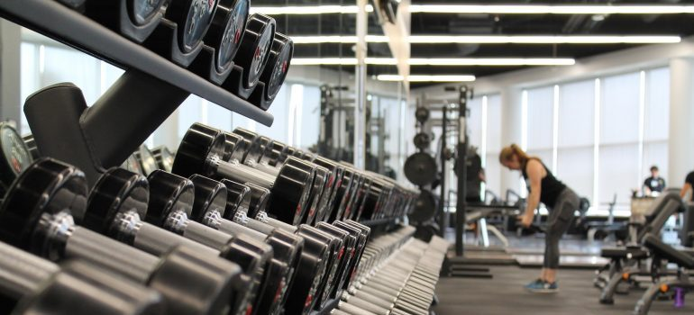 dumbbells and other gym equipment and a woman in the background
