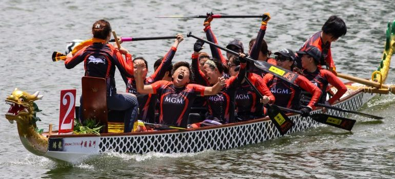 A team of chinese dragon boat rowers rowing.