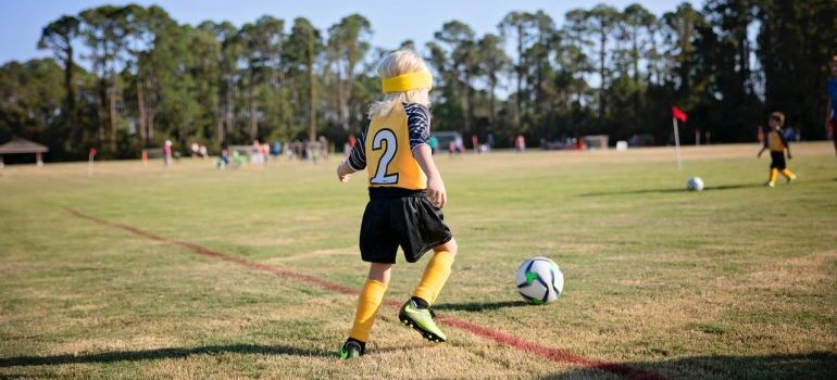 a child in a yellow and black jersey kicking the ball on a football field