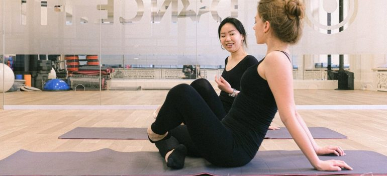 two women sitting on exercise matts talking to eachother