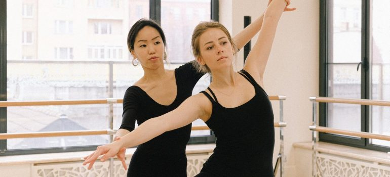 a dance teacher showing her student the proper posture for a dance move
