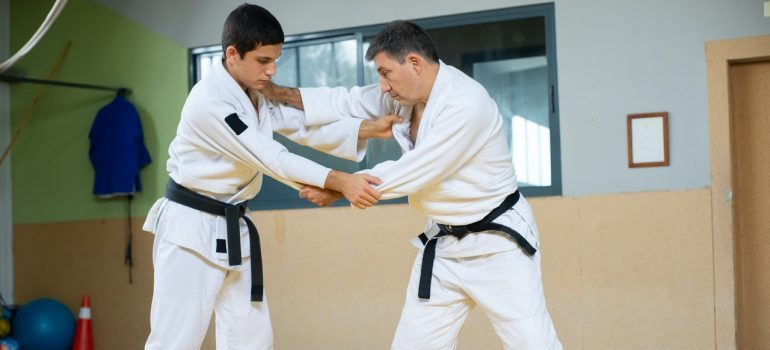 a trainer teaching a trainee karate moves