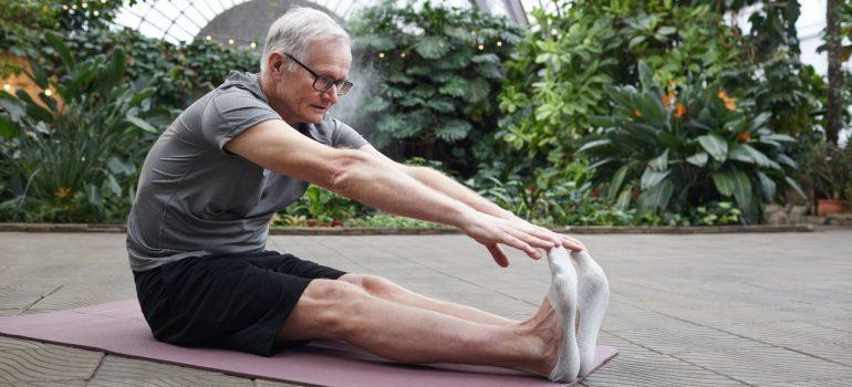 man stretching on yoga mat