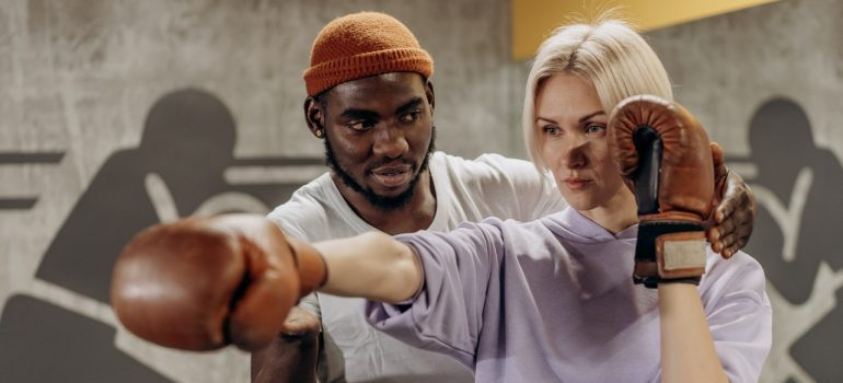 man teaching a woman to box