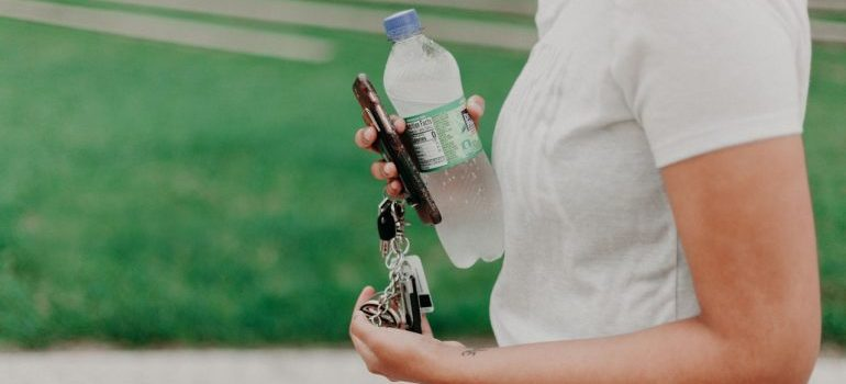 A woman carrying a bottle of water.