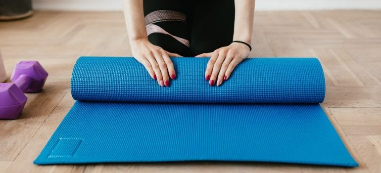 a woman rolling a yoga mat on the floor