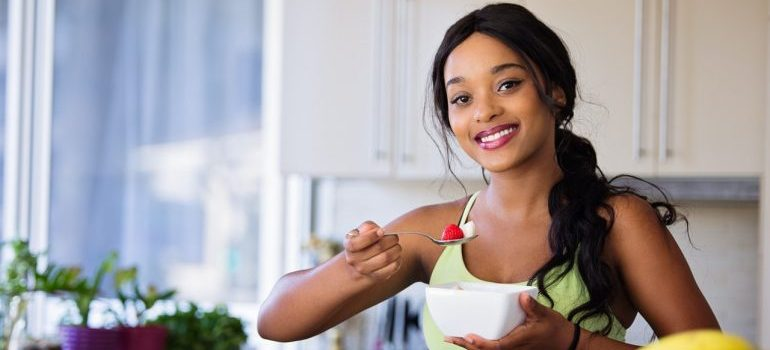 A young woman eating healthiy food since she knows both training and diet are important for weight loss!