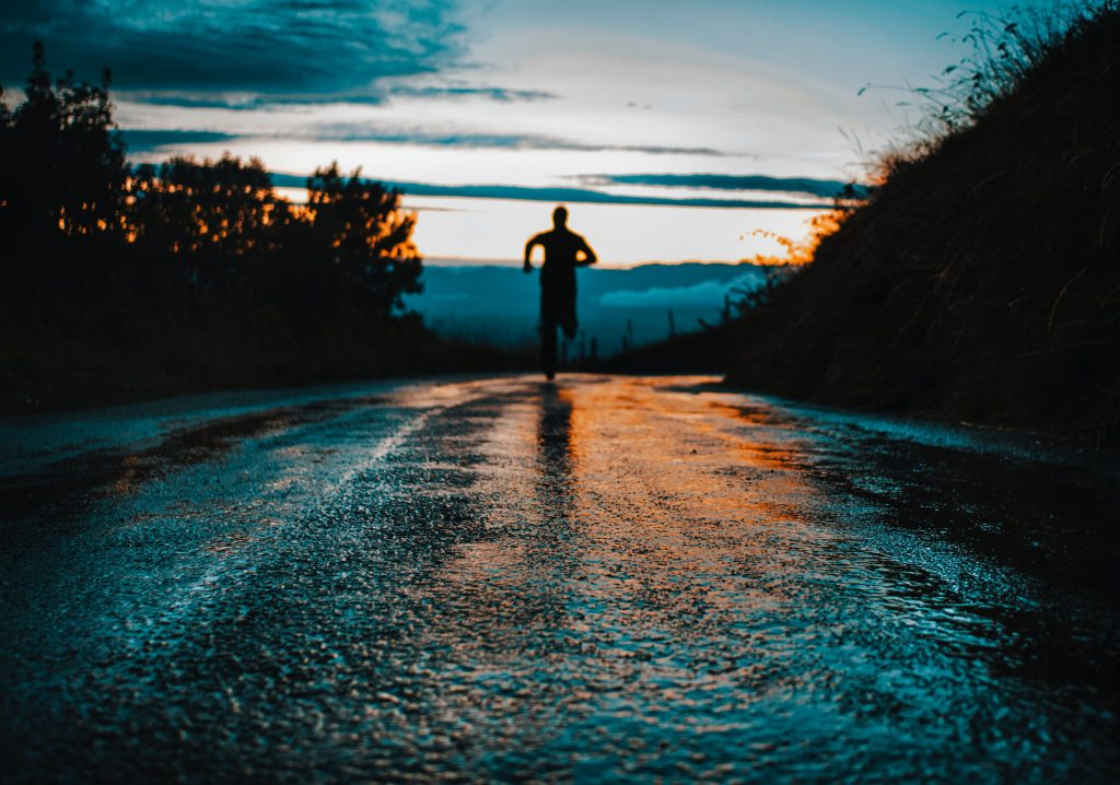 a man running on a road in the morning