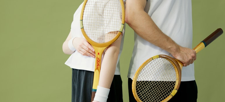 Couple holding squash racquets