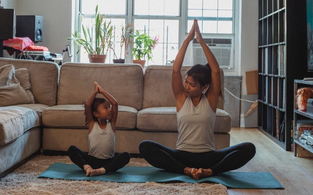 Mother with a daughter stretching out and doing yoga in the living room.