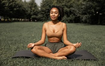 A woman doing breathing exercises in nature since she's aware of the profound power of breathing in yoga.