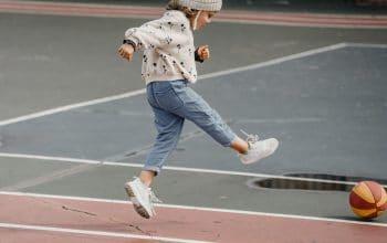 A little girl kicking a ball.