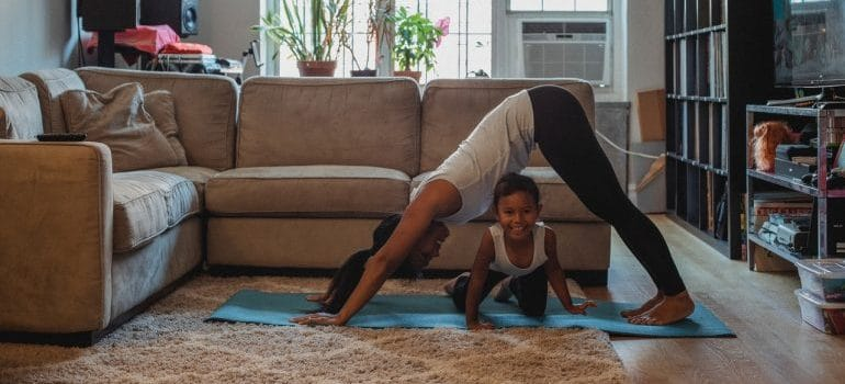 A mother and her daughter doing yoga.