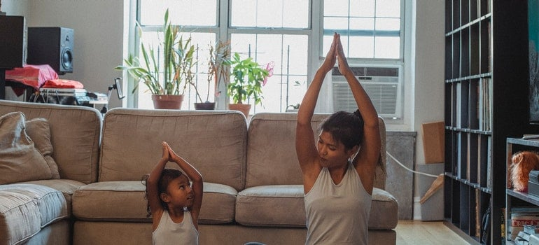 A child and a woman are doing yoga exercises on the floor.