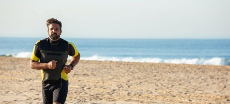 A man running at a beach.