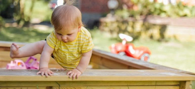baby crossing over a fence