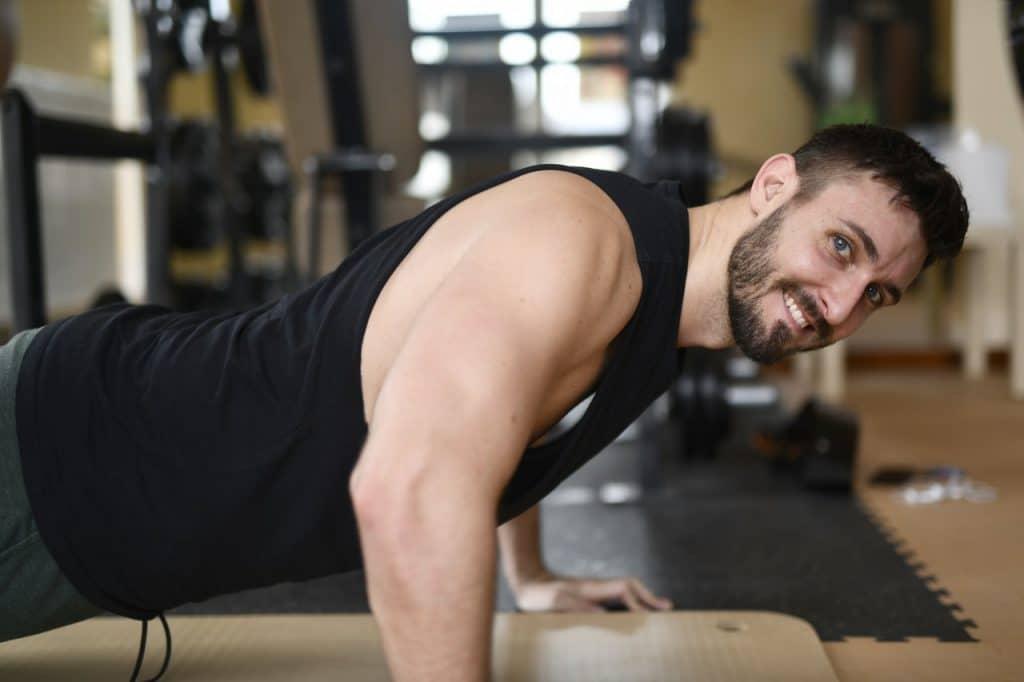 a man looking at a camera while doing push-ups