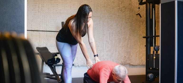 A woman is helping a man while he is stretching.