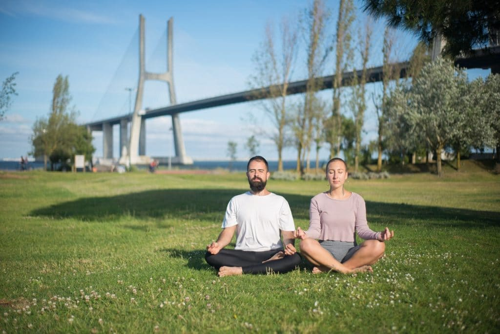 man and woman meditating on the grass