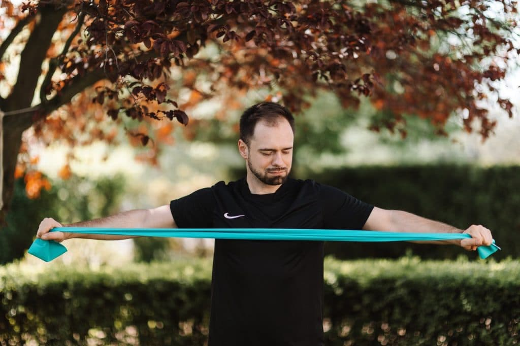 Guy stretching the resistance band.