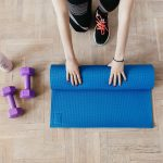 a woman rolling up a yoga mat