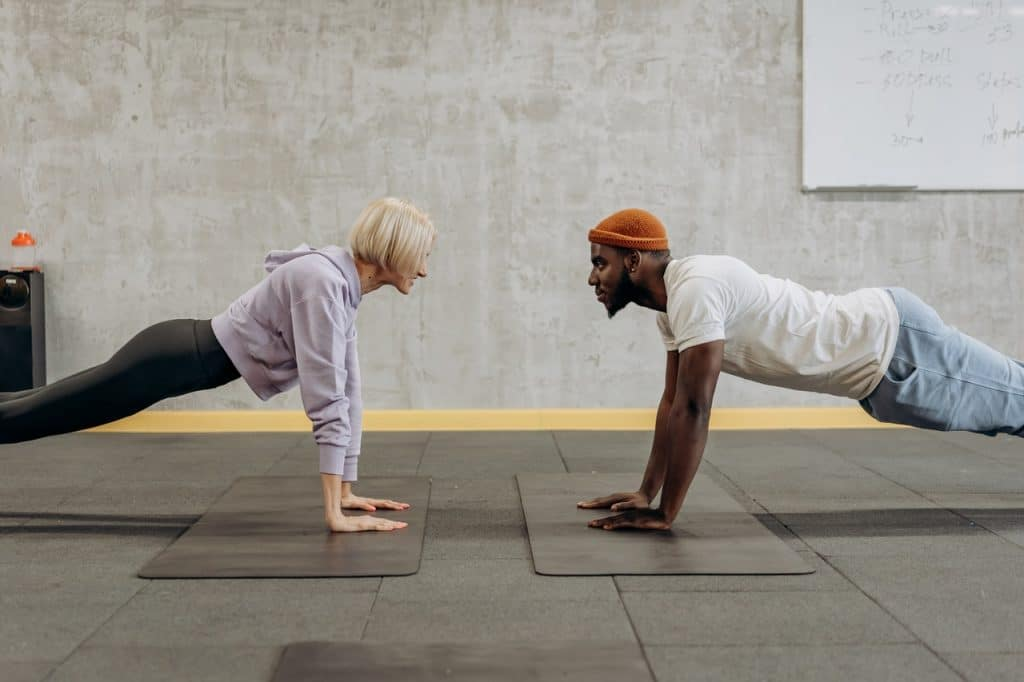 a woman teaching a man how to do a push-up plank after complaining that push-ups feel impossible