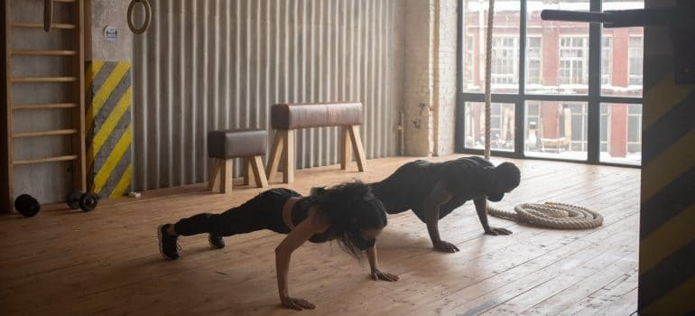 two people doing push-ups in a gym